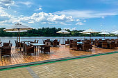 picturesque view of outdoor cafe with rattan chairs and tables on shore of river