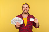 Bank loan, financial savings and commerce. Cheerful hipster guy in checkered shirt holding dollar bills
