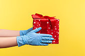 Profile side view closeup of human hand in blue surgical gloves holding red gift box. sharing, giving or delivery concept.