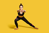 Athletic pretty girl with hair bun in tight sportswear doing sport, lower-body exercise, stretching hands out