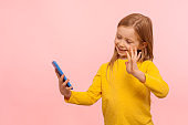 Portrait of happy beautiful little girl with ginger hair smiling and gesturing hi hello to mobile phone