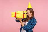 Portrait of curious girl with party cone on head looking inside present box with nosy expression