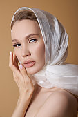 Beautiful beauty blonde woman with a large white head scarf, white cloth