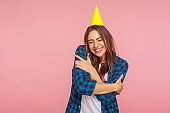 Fascinating girl with funny party cone hugging oneself with expression of pleasure and love, celebrating birthday