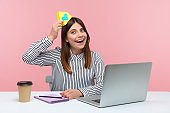 Positive smiling brunette woman freelancer in striped shirt sitting at workplace holding paper house on head, working from home, telework