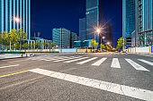 Empty asphalt road through modern city at night