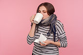 Flu treatment. Portrait of ill young woman wrapped in scarf drinking hot tea beverage, taking pills to treat