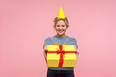 Happy birthday! Portrait of cheerful woman with funny cone hat on head and in warm sweater offering wrapped present box