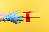 Profile side view closeup of human hand in blue surgical gloves holding yellow gift box.