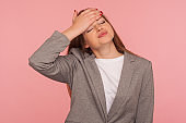 Facepalm. Portrait of forgetful upset young woman in business suit touching her forehead with sorrowful expression