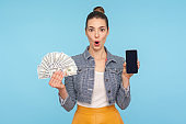 Unbelievable mobile payment service. Portrait of surprised woman with hair bun holding cellphone and dollar bills