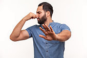 Confused unhappy bearded man grabbing nose with fingers and stretching hand out feeling disgusted unpleasant smell