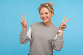 Excited cheerful woman with short curly hair in sweatshirt showing victory gesture, double peace sign