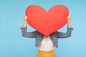 Anonymous woman in casual outfit hiding face behind huge red heart, concept of secret love, unknown lover and affair
