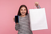 Online store app. Portrait of happy woman in striped sweatshirt holding shopping bag and cell phone, showing mobile device