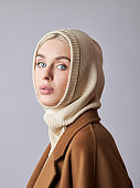 European Muslim woman with a blonde hair in a bonnet hood dressed on her head. Beautiful girl with soft skin, natural cosmetics