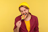 Excited hipster guy in beanie hat and checkered shirt biting lollipop candy, looking with crazy expression, craving