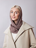 European Muslim woman with a blonde hair in a headscarf shawl dressed on her head. Beautiful girl in coat with soft skin, natural cosmetics