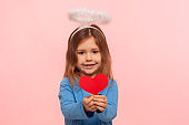 Portrait of adorable cute preschool girl with angelic nimbus holding paper heart and smiling to camera