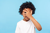 Portrait of funny nosy adorable little boy with curly hair covering face with hand and looking through fingers