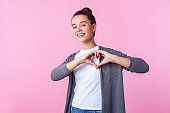 Portrait of lovely brunette teenage girl showing heart shape with hands. indoor studio shot isolated, pink background