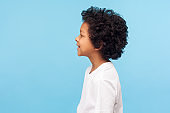 Profile of happy little boy with curly hair in T-shirt smiling carefree and looking to side copy space