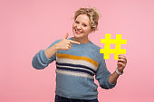 Look at hashtag. Portrait of cute happy woman with short curly hair in warm sweater pointing at big yellow hash sign
