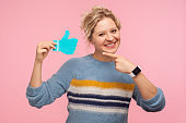 Like button. Portrait of cheerful woman in warm sweater pointing at thumbs up blue icon, follower notification