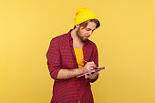 Hipster trendy guy in beanie hat looking inspired by creative idea, eager writing thought reminder to-do list into notebook