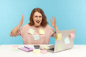 Stressful job. Depressed overworked woman employee in glasses covered with sticky notes, angrily raising hands