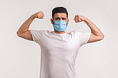 Man in hygienic mask showing strength and immunity to recover from contagious disease