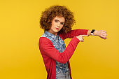 Portrait of busy impatient woman with curly hair showing wrist watch and looking angrily at camera