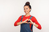 I love you! Portrait of attractive joyful girl with hair bun in denim overalls making heart shape with fingers
