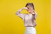 Stinky smell. Portrait of young dissatisfied woman with fair hair in casual beige blouse, isolated on yellow background