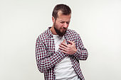 Heart attack, cardiological problems. Portrait of stressed out bearded man grabbing chest suffering acute pain cramp. white background