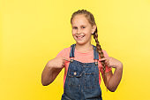 This is me! Portrait of cheerful confident little girl in denim overalls pointing herself, selfishly paying attention to own merits