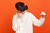 Serious concentrated man in casual style white hoodie and virtual reality headset holding clenched fists up ready to boxing, online gaming
