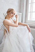 Bride woman in a light summer wedding dress sitting at the window and waiting for the wedding ceremony. Girl with perfect hair and beautiful makeup