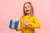 Portrait of delighted amazed little girl pointing gift box, boasting present and looking with astonishment to camera