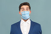 Closeup portrait of surprised or shocked young man with surgical medical mask looking at camera with big eyes.