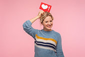 Portrait of cheerful adult woman with curly hair in warm sweater holding heart Like icon over head, love content