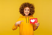 Internet blogging. Portrait of joyful curly-haired woman in urban style hoodie pointing at heart like icon