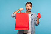 Amazed shocked man holding shopping bags and cell phone with mock up, blank display for advertisement
