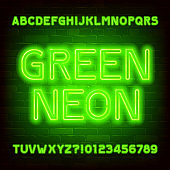 Green Neon alphabet font. Simple neon color letters and numbers. Brick wall background.