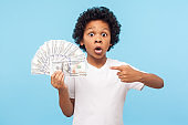 Wow, I'm rich! Amazed lucky wealthy little boy with curly hair pointing to fan of dollar banknotes