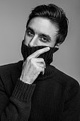 Portrait of stylish handsome young man in warm sweater, covering mouth with high collar and looking pensive