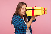 Portrait of curious cheerful girl in checkered shirt looking inside present box with nosy expression, peeking with interest