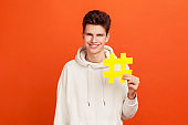 Handsome cheerful teenager in casual hoodie holding hashtag symbol with toothy smile on face, social media influence