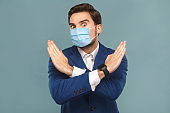 Stop, no! Portrait of young man with surgical medical mask standing. showing hand ban close at camera.
