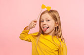 Portrait of playful adorable little ginger girl holding paper bow and sticking out tongue, naughty child having fun
